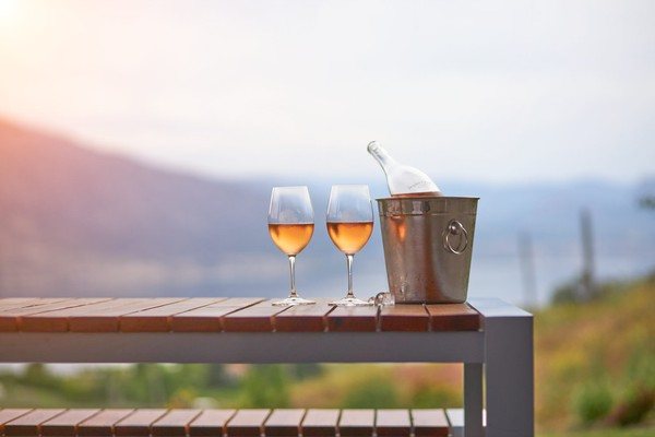 Two glasses of Rose and a bottle of wine on a picnic table at sunset